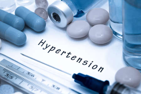 Hypertension - diagnosis written on a white piece of paper. Syringe and vaccine with drugs Stock Photo