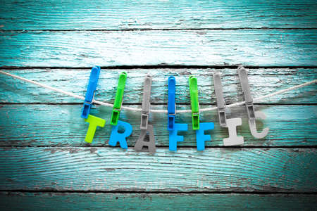 optimizer: word traffic fasten clothespins on a rope behind a wooden background