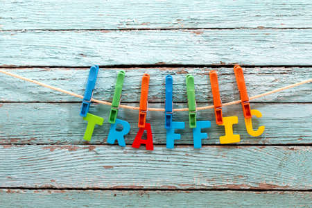 the optimizer: word traffic fasten clothespins on a rope behind a wooden background