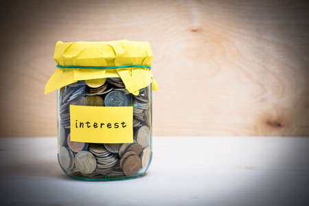 money jar: Financial concept. Coins in glass money jar with interest label. Wooden background