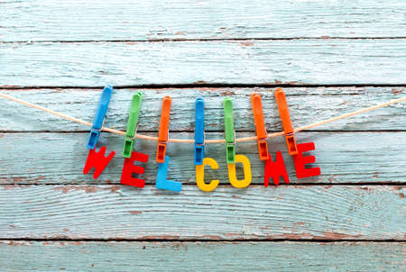 word welcome fasten clothespins on a rope behind a wooden background Standard-Bild