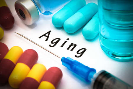 oldness: Aging - diagnosis written on a white piece of paper. Syringe and vaccine with drugs Stock Photo