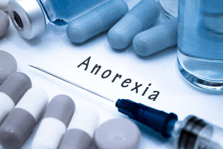 anorexia: Anorexia - diagnosis written on a white piece of paper. Syringe and vaccine with drugs. Stock Photo