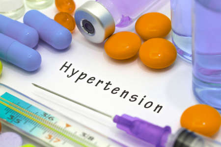 healthy arteries: Hypertension - diagnosis written on a white piece of paper. Syringe and vaccine with drugs Stock Photo