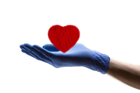 outstretched hand: Heart symbol in the outstretched hand of the doctor with gloves on a white background. The concept of patient care. Stock Photo