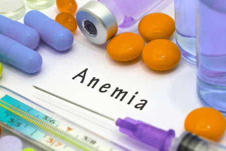 anemia: Anemia - diagnosis written on a white piece of paper. Syringe and vaccine with drugs.