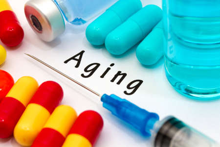 Aging - diagnosis written on a white piece of paper. Syringe and vaccine with drugs Stock Photo