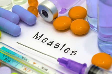 measles: Measles - diagnosis written on a white piece of paper. Syringe and vaccine with drugs. Stock Photo