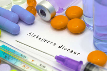 aging brain: Alzheimers disease - diagnosis written on a white piece of paper. Syringe and vaccine with drugs. Stock Photo