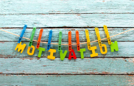 motivation: word motivation fasten clothespins on a rope behind a wooden background