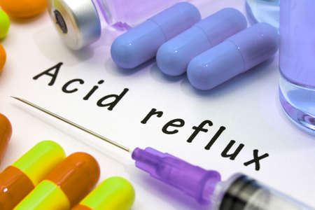Acid reflux - diagnosis written on a white piece of paper. Syringe and vaccine with drugs.