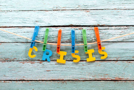 subprime mortgage crisis: word crisis fasten clothespins on a rope behind a wooden background Stock Photo