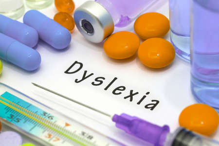 dyslexia: Dyslexia - diagnosis written on a white piece of paper. Syringe and vaccine with drugs.