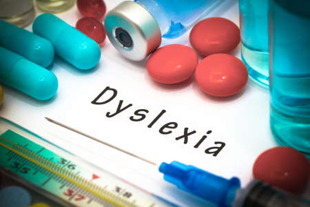 developmental disorder: Dyslexia - diagnosis written on a white piece of paper. Syringe and vaccine with drugs.