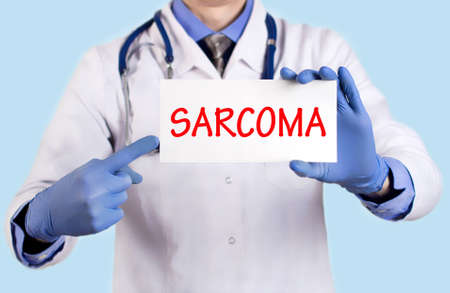 submucosa: Doctor keeps a card with the name of the diagnosis – sarcoma. Selective focus. Medical concept.