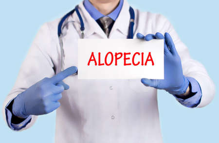 keeps: Doctor keeps a card with the name of the diagnosis – alopecia. Selective focus. Medical concept.