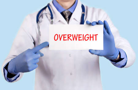 keeps: Doctor keeps a card with the name of the diagnosis � overweight. Selective focus. Medical concept.