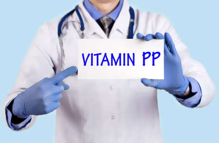 pp: Doctor keeps a card with the name of the Vitamin PP. Selective focus. Medical concept.