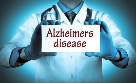brain aging: Doctor keeps a card with the name of the diagnosis � alzheimers disease. Selective focus. Medical concept. Stock Photo