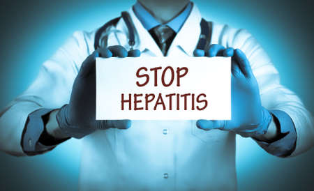 Doctor keeps a card with the name of the - stop hepatitis. Selective focus. Foto de archivo