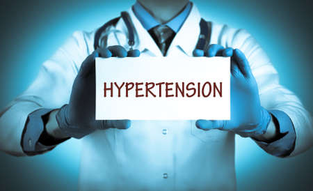 Doctor keeps a card with the name of the diagnosis – hypertension. Selective focus. Medical concept.