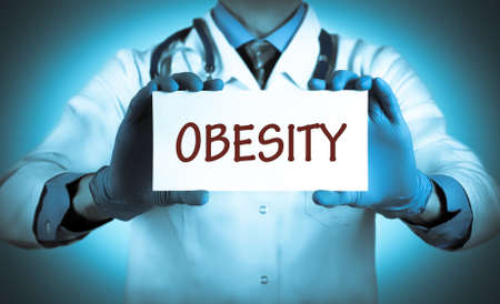 keeps: Doctor keeps a card with the name of the diagnosis � obesity. Selective focus. Medical concept. Stock Photo
