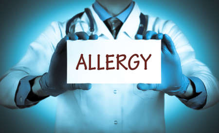 hypersensitivity: Doctor keeps a card with the name of the diagnosis � allergy. Selective focus. Medical concept.