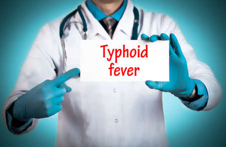 keeps: Doctor keeps a card with the name of the diagnosis � typhoid fever. Selective focus. Medical concept.