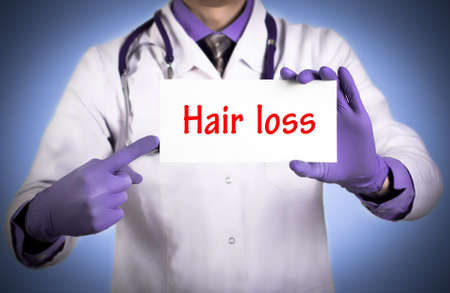 thinning: Doctor keeps a card with the name of the diagnosis – hair loss. Selective focus. Medical concept. Stock Photo