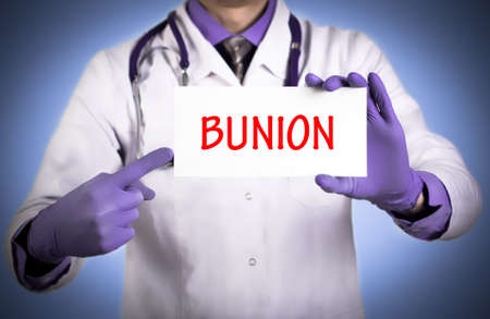 Doctor keeps a card with the name of the diagnosis – bunion. Selective focus. Medical concept.
