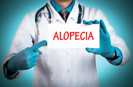 keeps: Doctor keeps a card with the name of the diagnosis � alopecia. Selective focus. Medical concept. Stock Photo