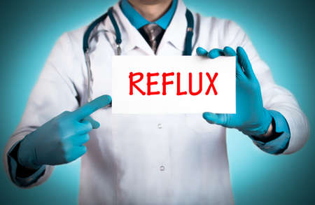 antacid: Doctor keeps a card with the name of the diagnosis – reflux. Selective focus. Medical concept. Stock Photo