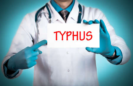 typhus: Doctor keeps a card with the name of the diagnosis – typhus. Selective focus. Medical concept.