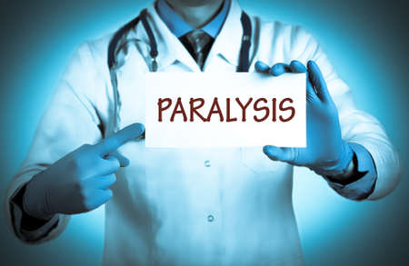 paralysis: Doctor keeps a card with the name of the diagnosis � paralysis. Selective focus. Medical concept.