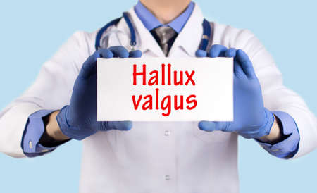 deformity: Doctor keeps a card with the name of the diagnosis – hallux valgus. Selective focus. Medical concept.