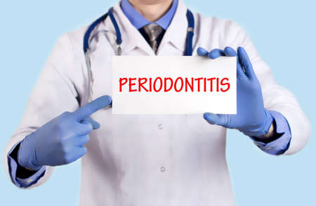 bacterial plaque: Doctor keeps a card with the name of the diagnosis � periodontitis. Selective focus. Medical concept.
