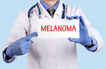 abnormal: Doctor keeps a card with the name of the diagnosis � melanoma. Selective focus. Medical concept.