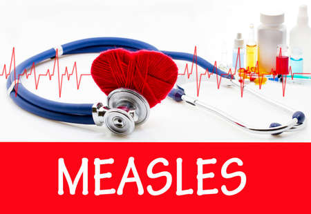det: The diagnosis of measles. Phonendoscope and vaccine with drugs. Medical concept. Stock Photo