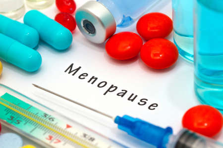 Menopause - diagnosis written on a white piece of paper. Syringe and vaccine with drugs. Stock Photo