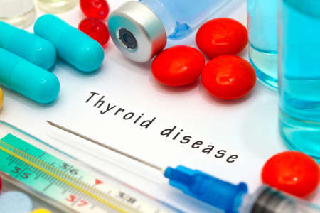 Thyroid disease - diagnosis written on a white piece of paper. Syringe and vaccine with drugs.