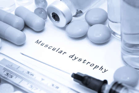 myopathy: Muscular dystrophy - diagnosis written on a white piece of paper. Syringe and vaccine with drugs.