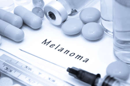 the lesions: Melanoma - diagnosis written on a white piece of paper. Syringe and vaccine with drugs.