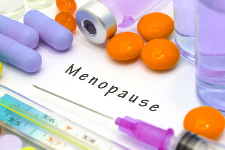 MENOPAUSE: Menopause - diagnosis written on a white piece of paper. Syringe and vaccine with drugs. Stock Photo