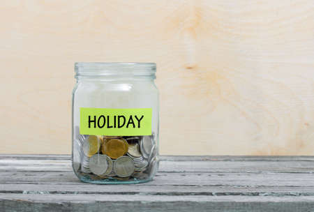 christmas budget: Label on a glass jar with the inscription - holiday. Glass jar with coins. Financial concept on wooden background