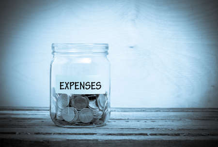 pay cuts: Label on a glass jar with the inscription - expenses. Glass jar with coins. Financial concept on wooden background