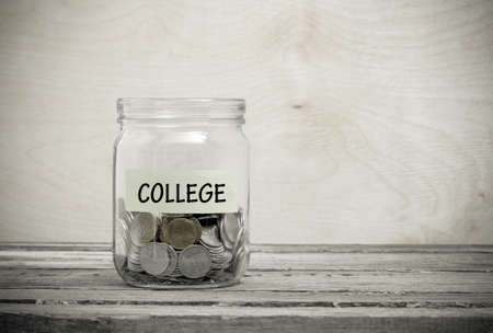 Label on a glass jar with the inscription - college. Glass jar with coins. Financial concept on wooden background Foto de archivo