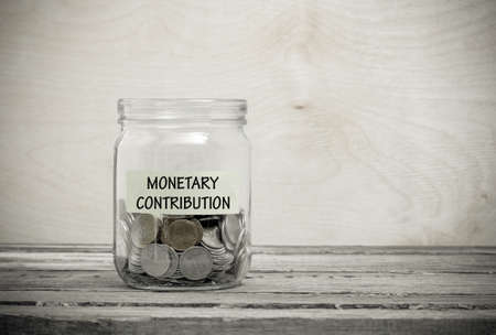 contribution: Label on a glass jar with the inscription - monetary contribution. Glass jar with coins. Financial concept on wooden background Stock Photo