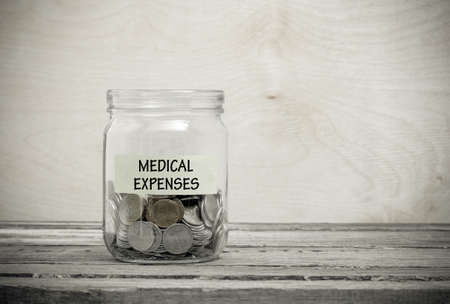 surgery costs: Label on a glass jar with the inscription - medical expenses. Glass jar with coins. Financial concept on wooden background Stock Photo