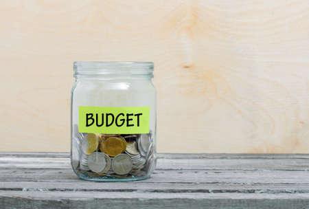 Beschriften Sie ein Glas auf Glas mit der Aufschrift - Budget. Glas mit Münzen. Finanzkonzept auf Holzuntergrund Standard-Bild