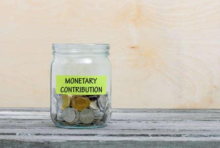 Etiqueta en un tarro de cristal con la inscripción - la contribución monetaria. Frasco de vidrio con monedas. Concepto financiero en el fondo de madera